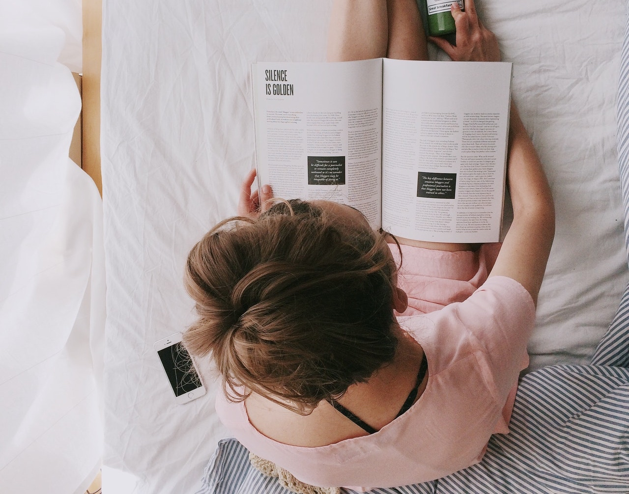 A White woman with a bun sitting on a white bed and reading a magazine that is sitting in her lap.