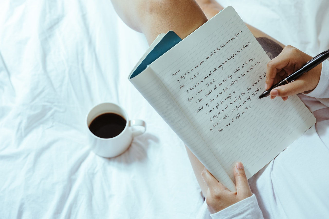 A woman sitting on a white bed holding a notebook and a pen with a cup of coffee sitting on the bed next to her.