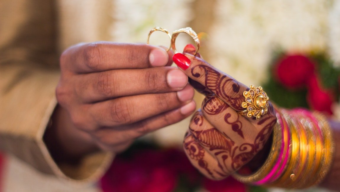 A man and a woman hold wedding rings, and the woman has heavy henna decorations and bangles on her hand.