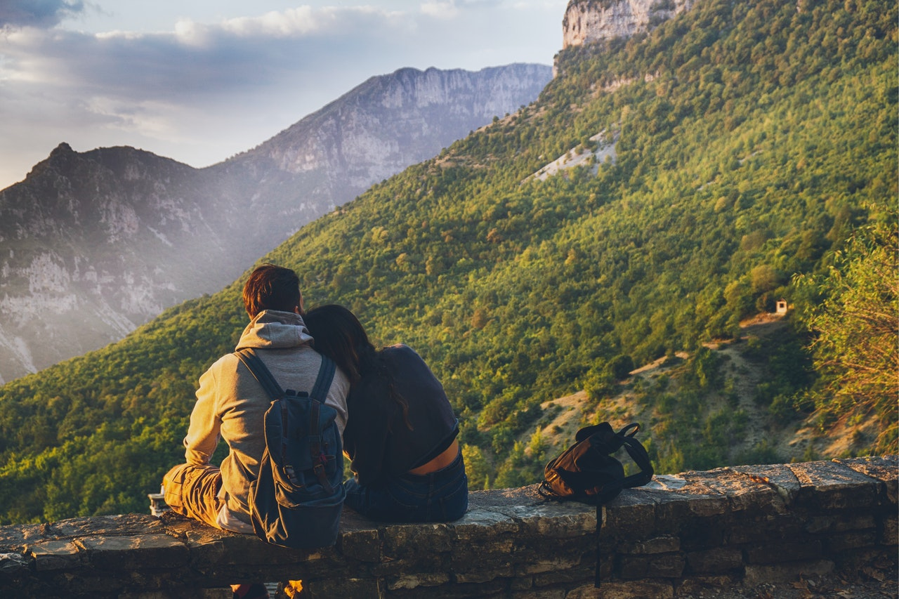 A male and female couple wearing backpacks while sitting closely and looking at green foggy mountains.