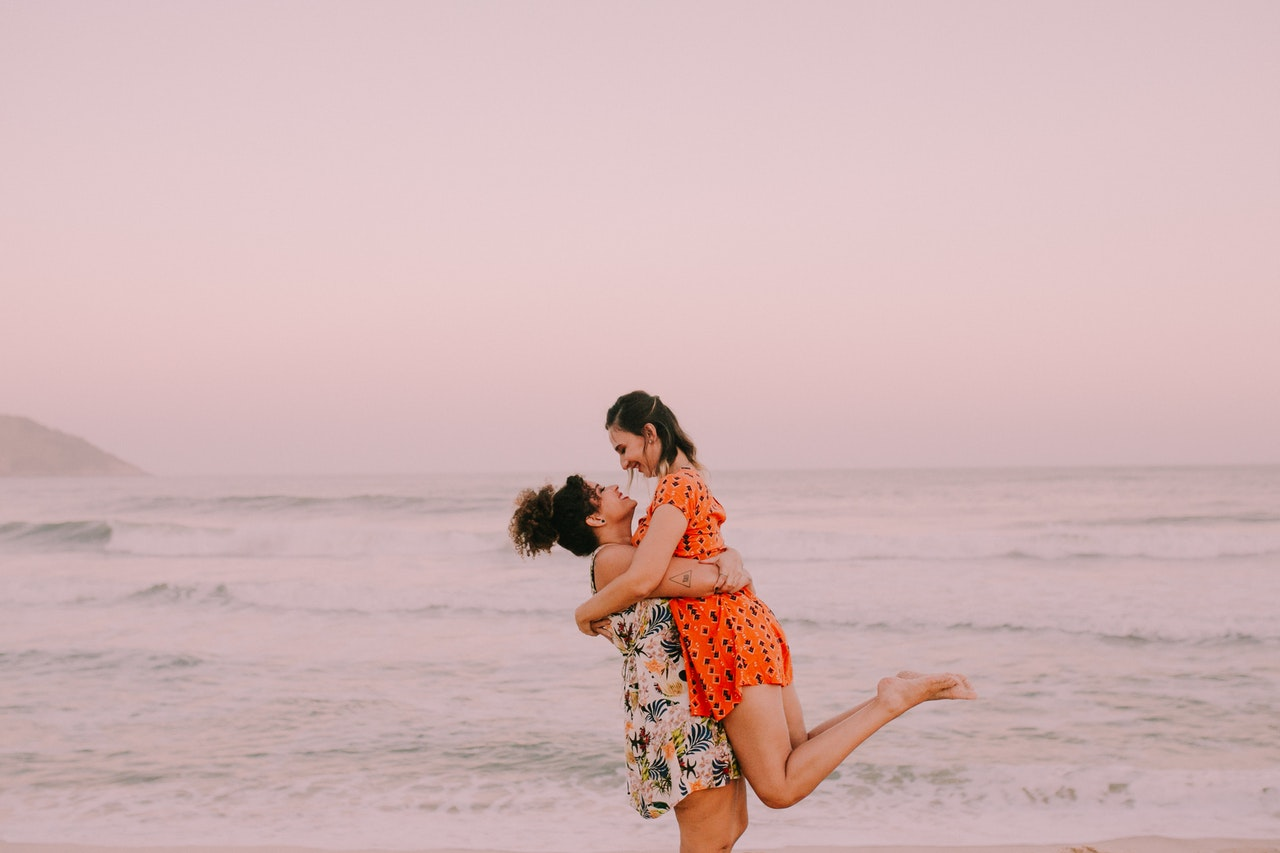 A female couple wearing dresses and embracing on the beach during sunset.