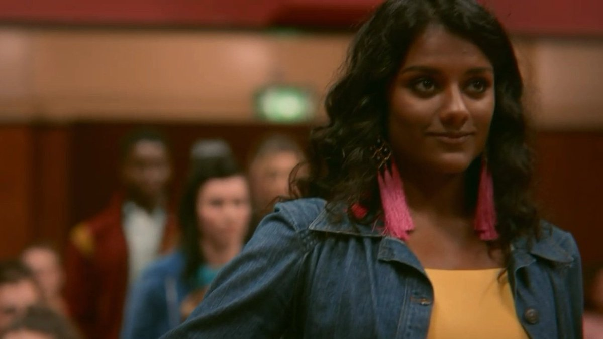 [Image description: Olivia from 'Sex Education' looking proudly at the camera and wearing a yellow top and pink earrings. ] Via Netflix
