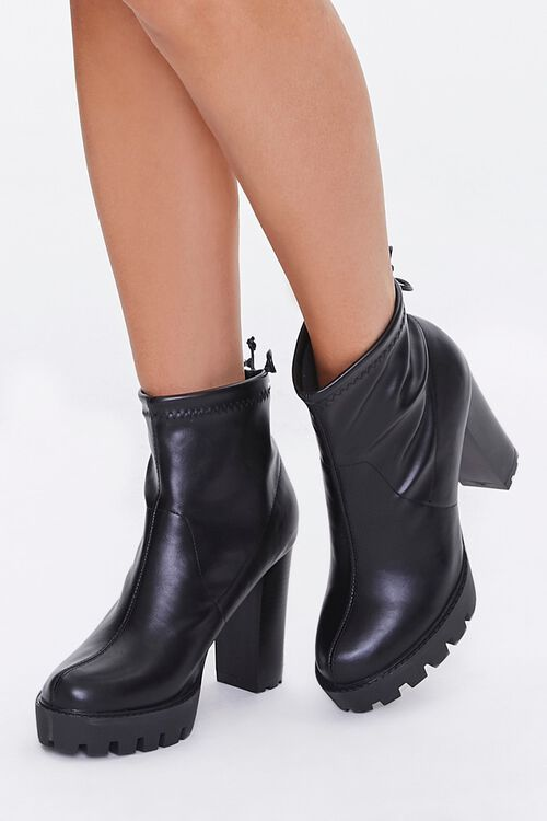A pair of black faux leather block booties.