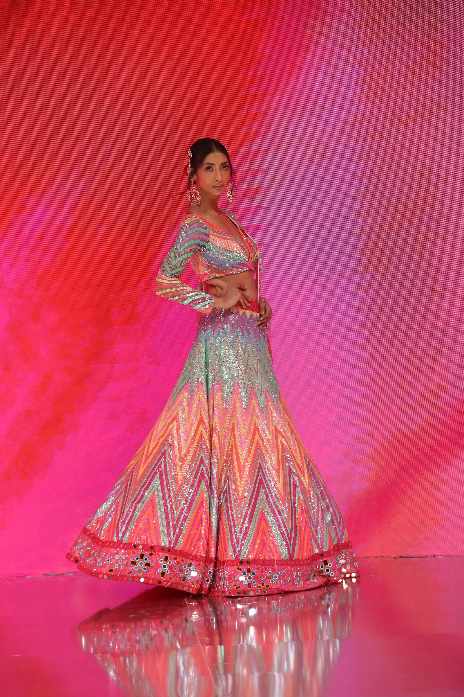 A lady wearing a striped, multi-colored lehenga that's covered in sequins and mirror work.