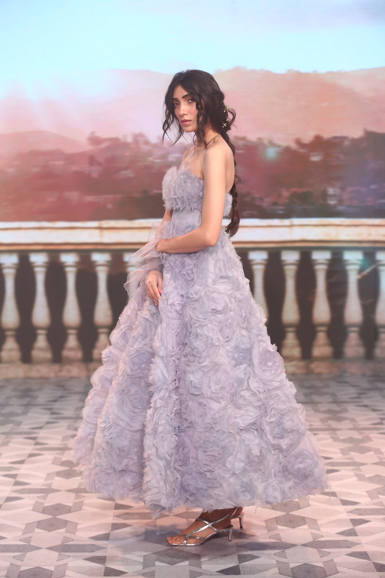 A lady wearing a floor-length lilac ball gown.