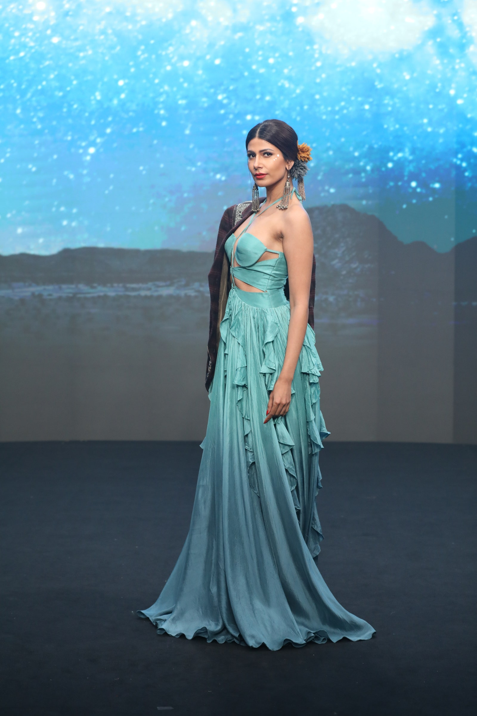 A lady wearing a floor-length turquoise gown.
