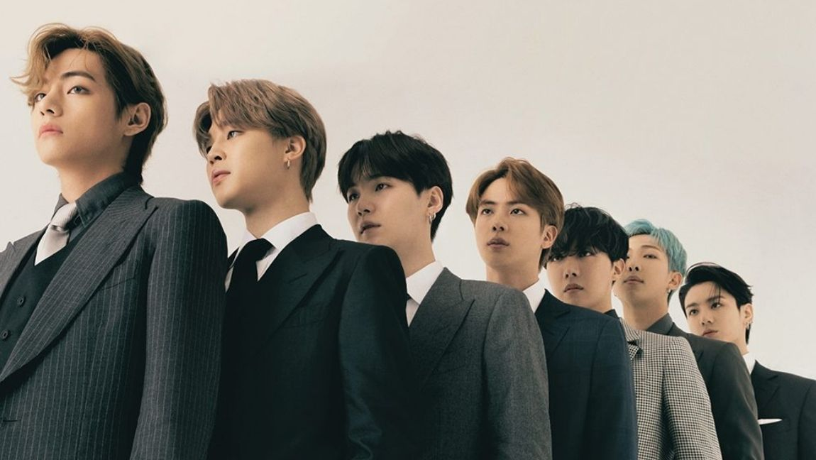 BTS standing in line, wearing formal suits and looking off into the distance.