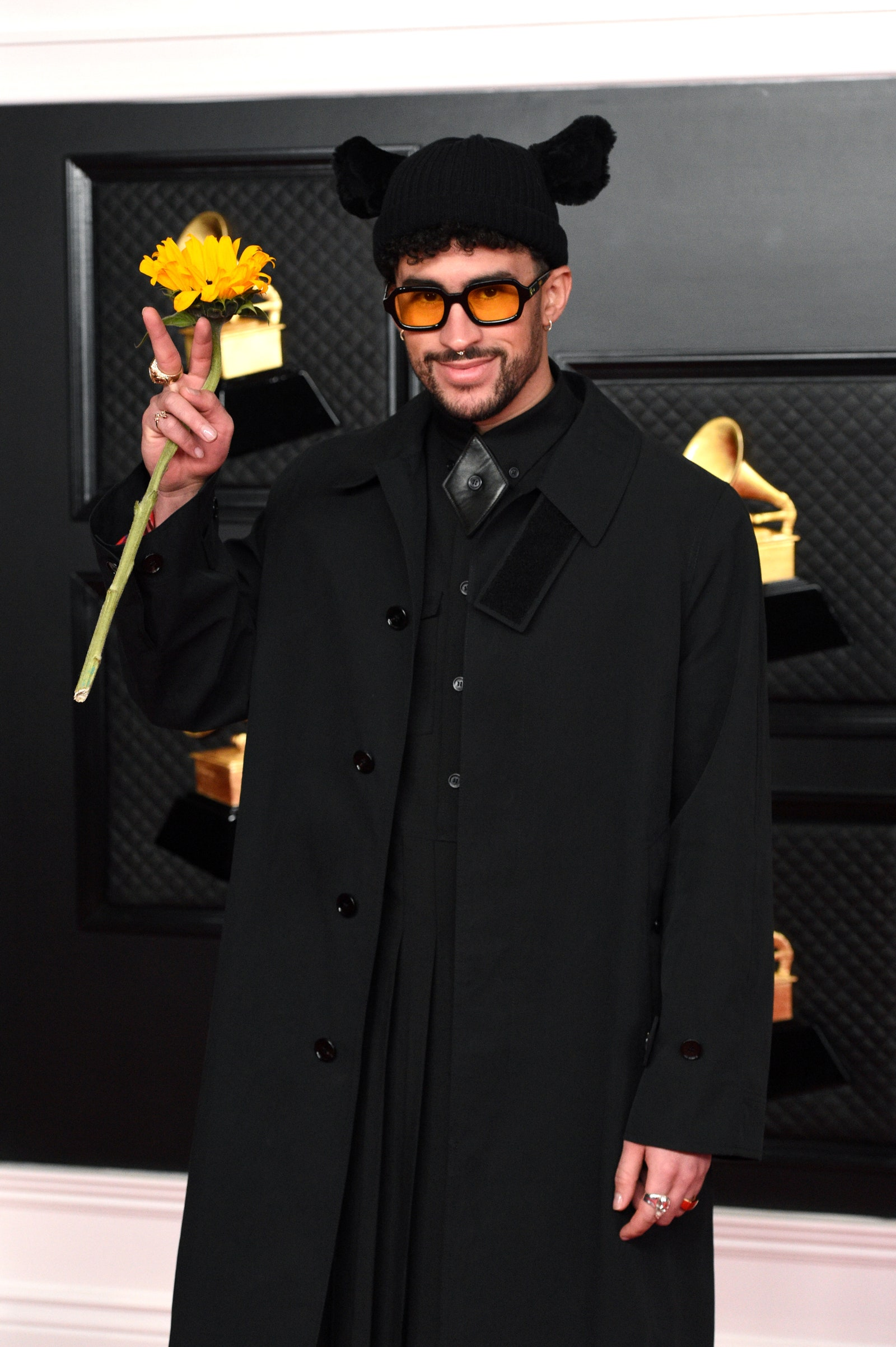 Bad Bunny holding a sunflower and posing on the carpet at the Grammys 2021.