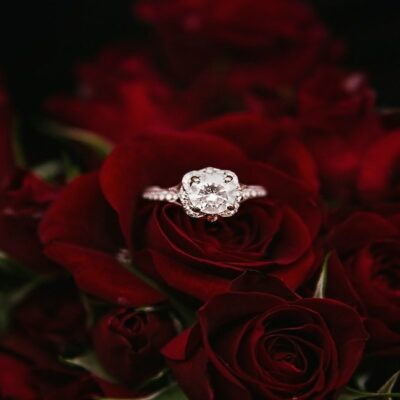 Diamond ring placed on top of red roses