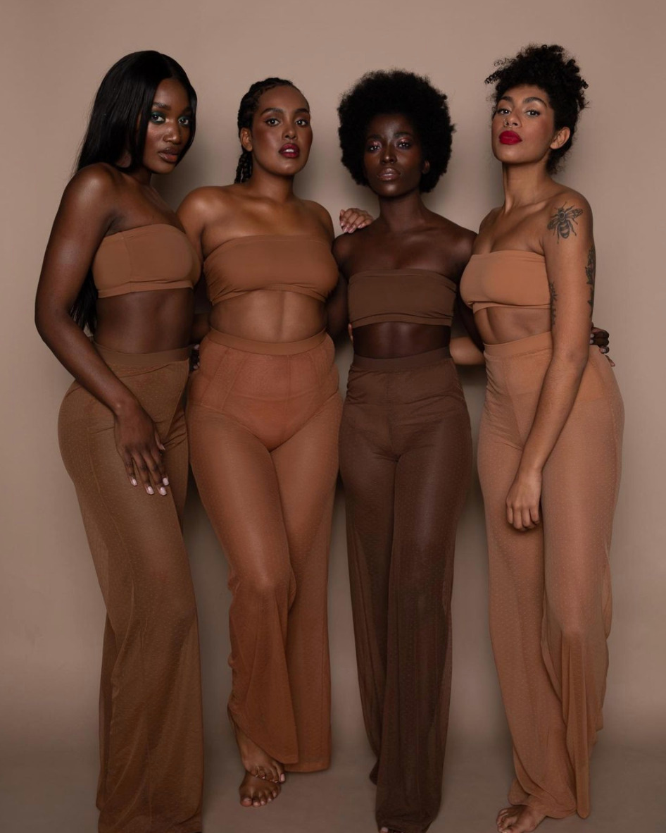 Four women are wearing bandeau tops and long lightweight trousers