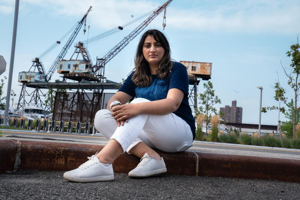 photo of sidra sitting on a pavement wearing atom's white sneakers