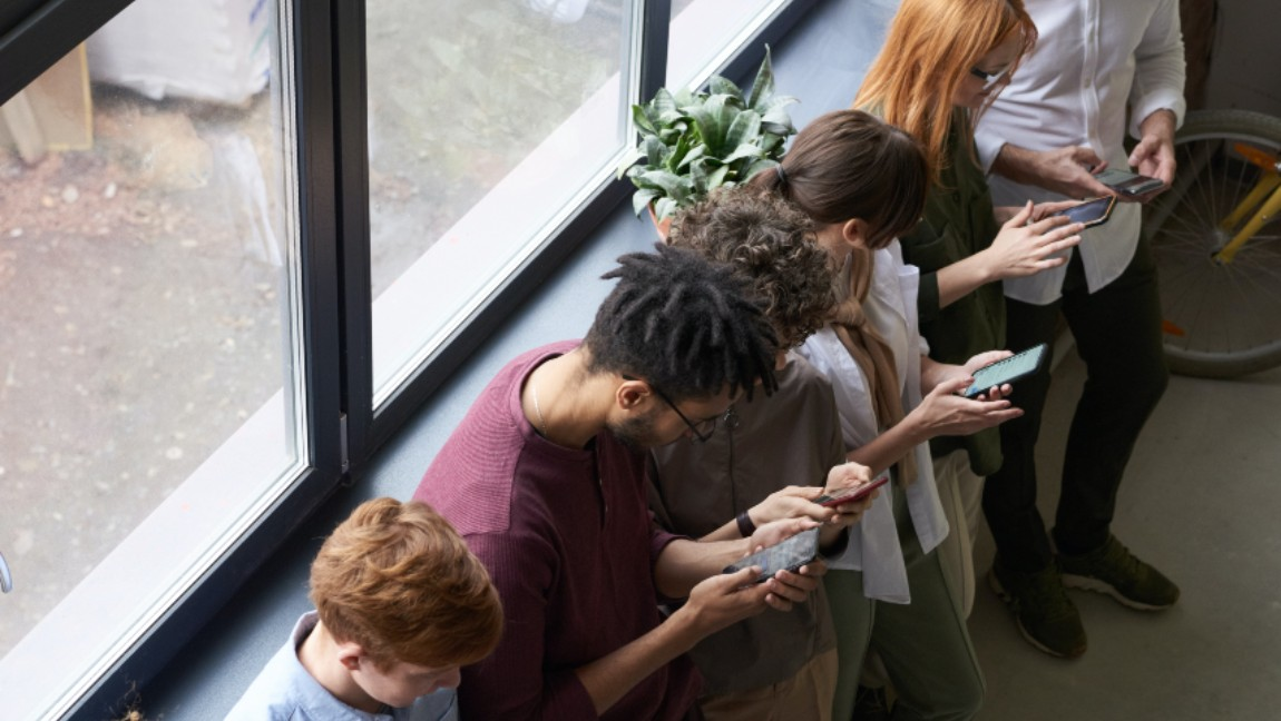 [Image description: People standing by windows are all on their phones.] Via Pexels.