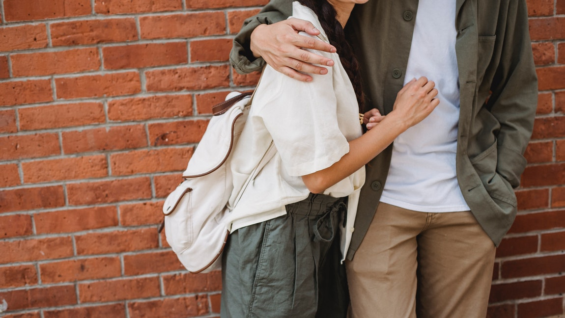 [Image Description: A couple stands in front of a brick wall.] Via Pexels