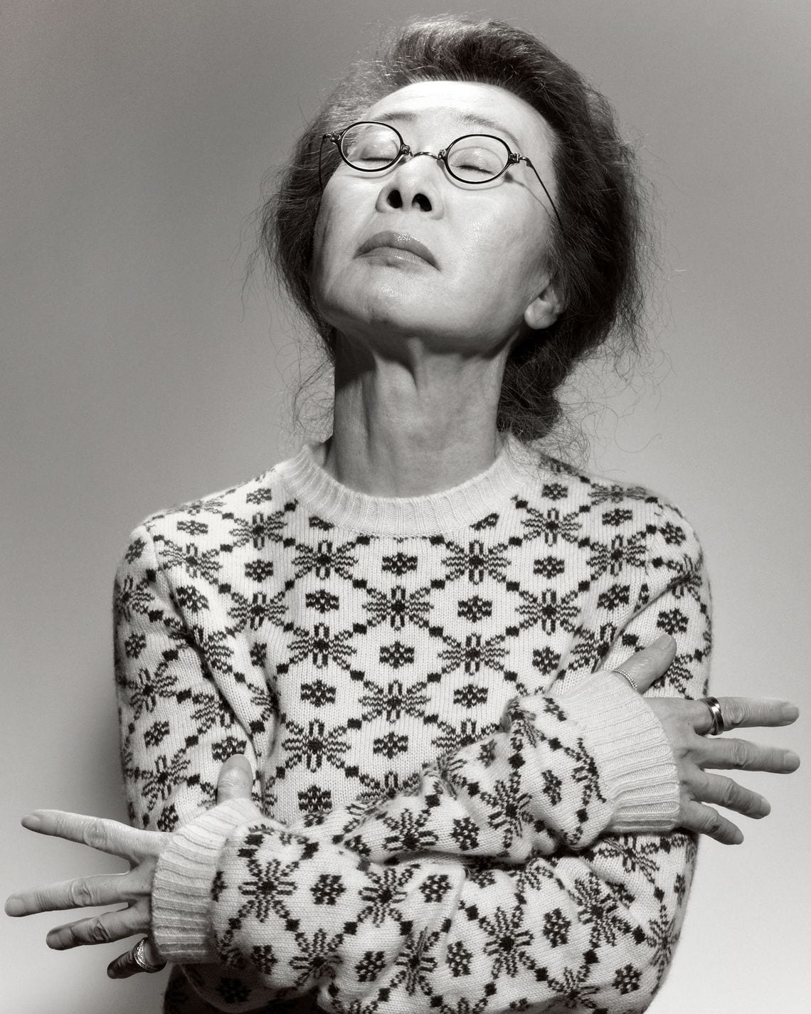 Youn Yuh-Jung in a floral sweater. Her hands are wrapped around her as she looks up to the sky, eyes closed. She looks deep in thought.