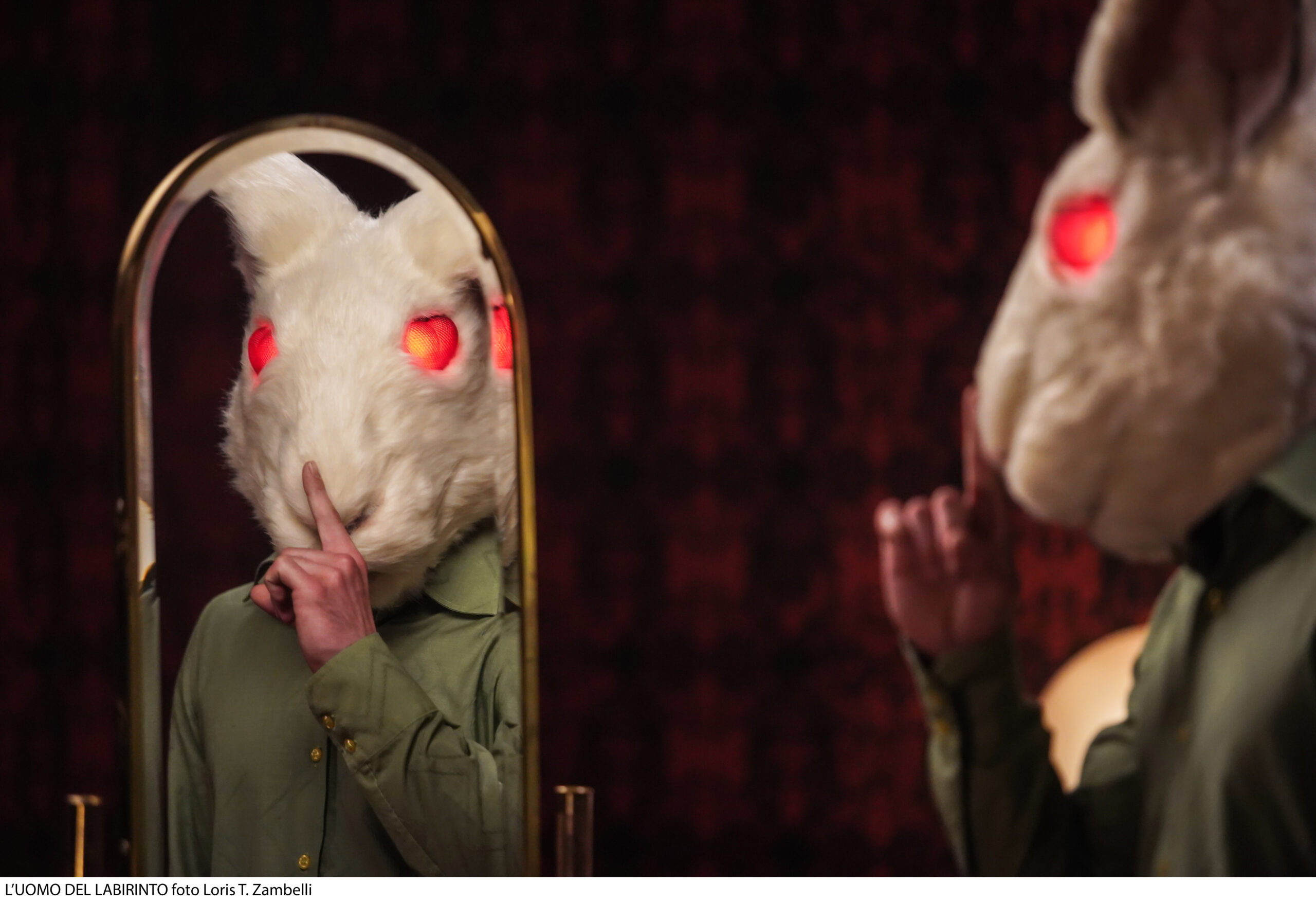 A photo of a character wearing the head of a bunny costume, holding his finger to his lips.