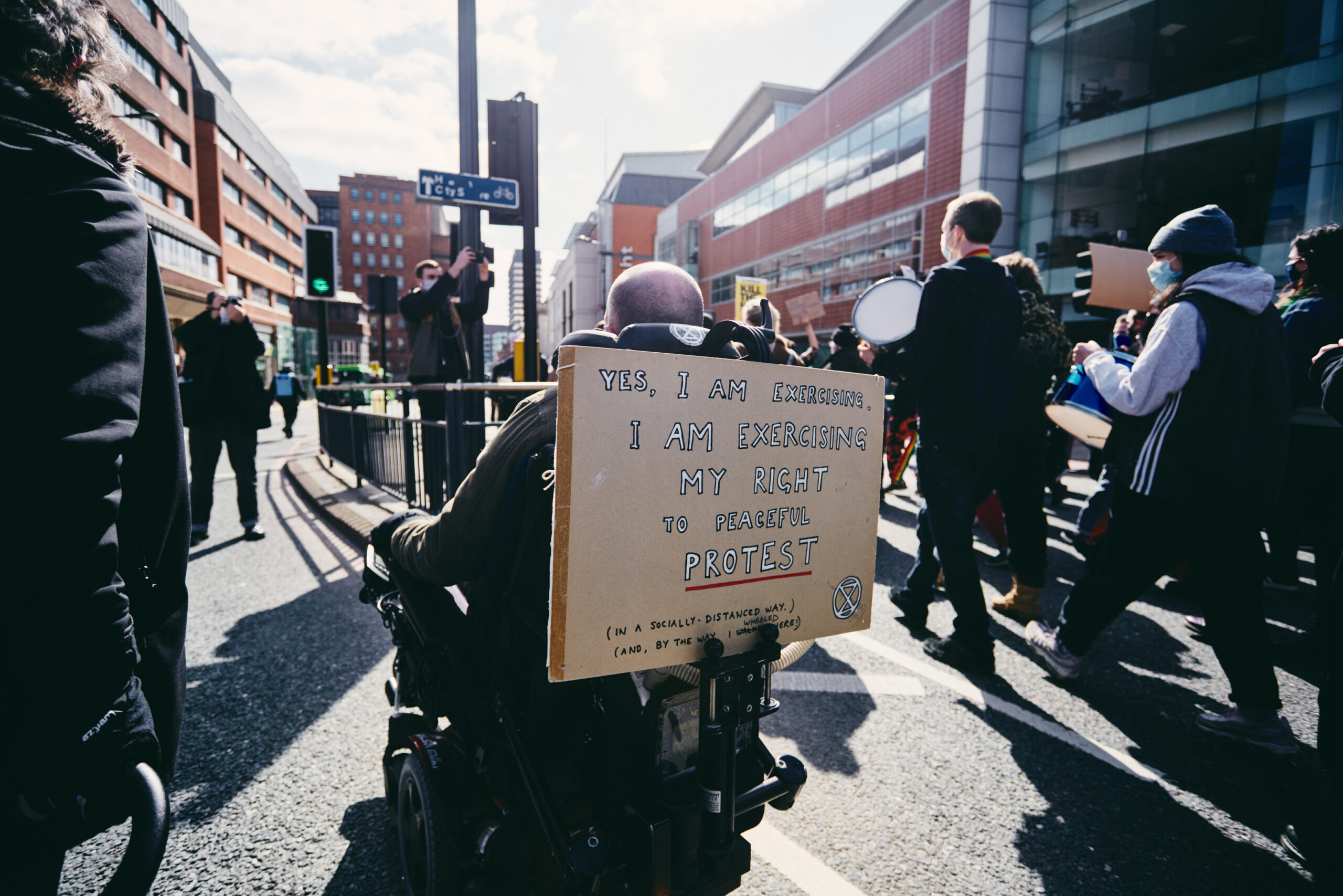 Protestor at the Kill the Bill protest in Leeds with a placard on the back of their wheelchair that says, 'Yes, I am exercising. I am exercising my right to peaceful protest.'
