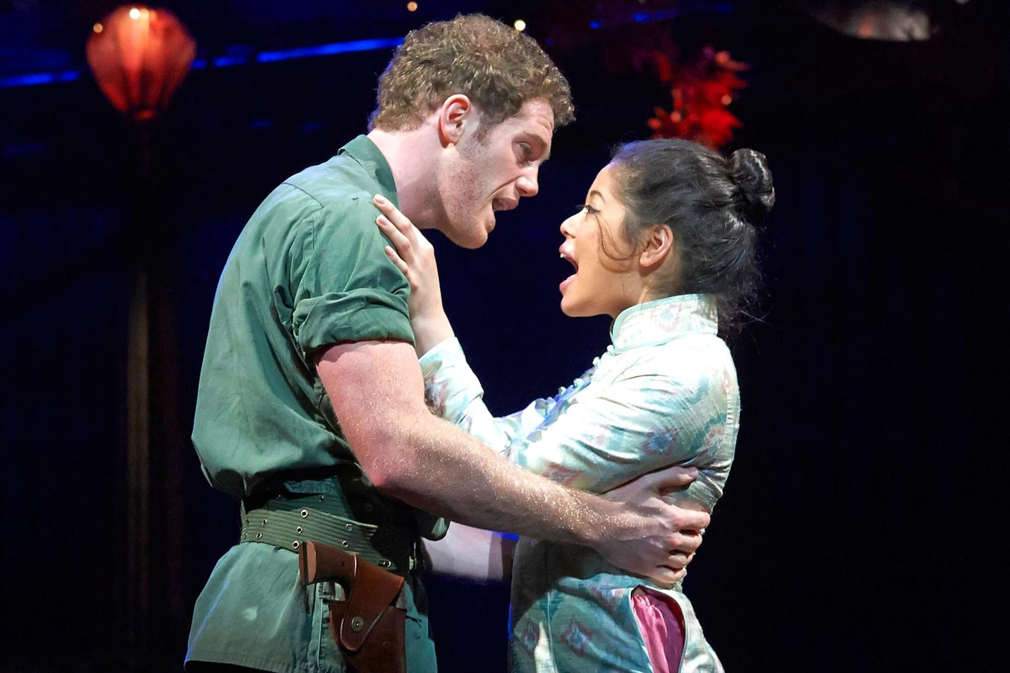"""A shot from the Broadway musical """"Miss Saigon"""". A man in an army uniform holds a Vietnamese woman in his arms. Both are singing."""
