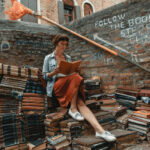 Woman reading in Libreria Acqua Alta, a bookstore in Venice that contains a set of steps made entirely out of books.