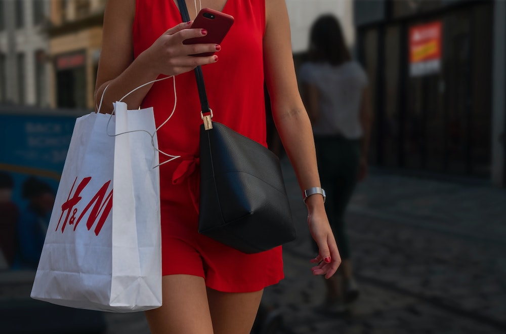 A woman walking outside wearing a red dress and carrying an H&M bag, wearing a black crossbody bag and holding her phone.