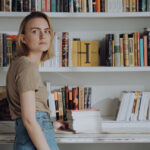 A woman stands in front of a bookshelf.
