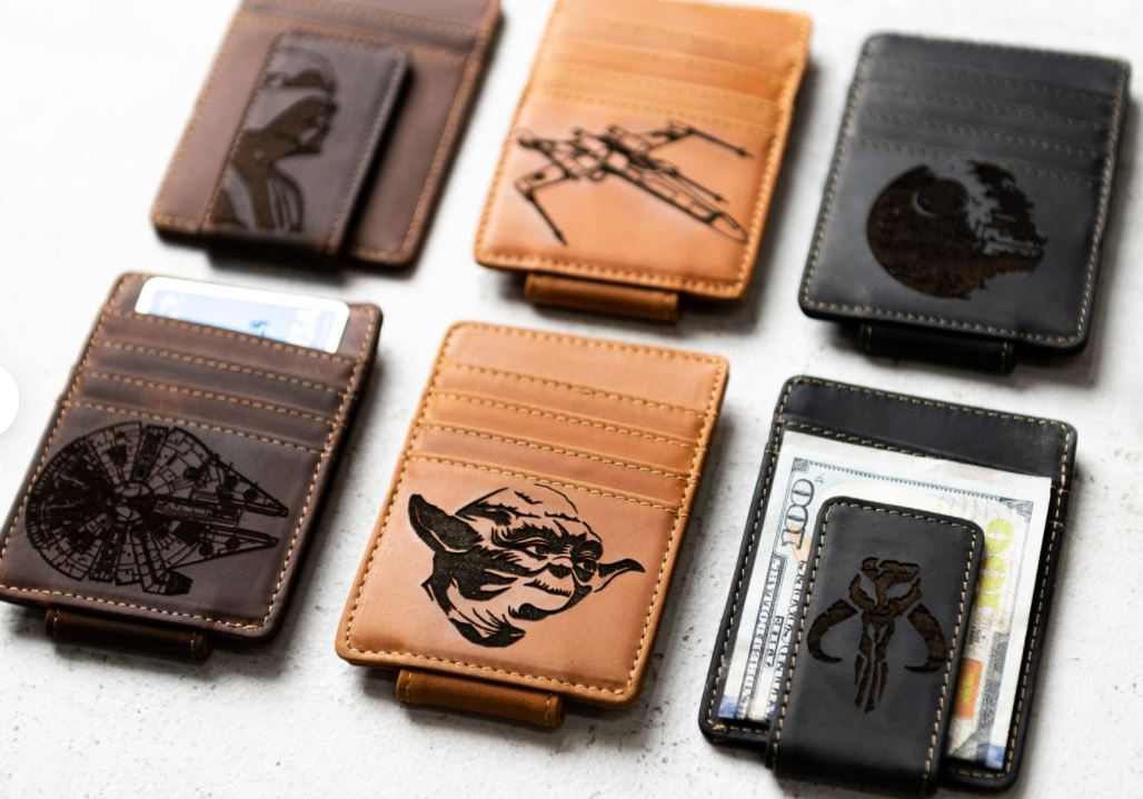 [Image description: A collage of 6 leather money clips with Star Wars illustrations] via Etsy