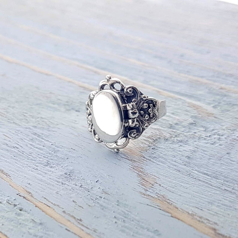 Sterling silver ring locket placed on a wooden surface.