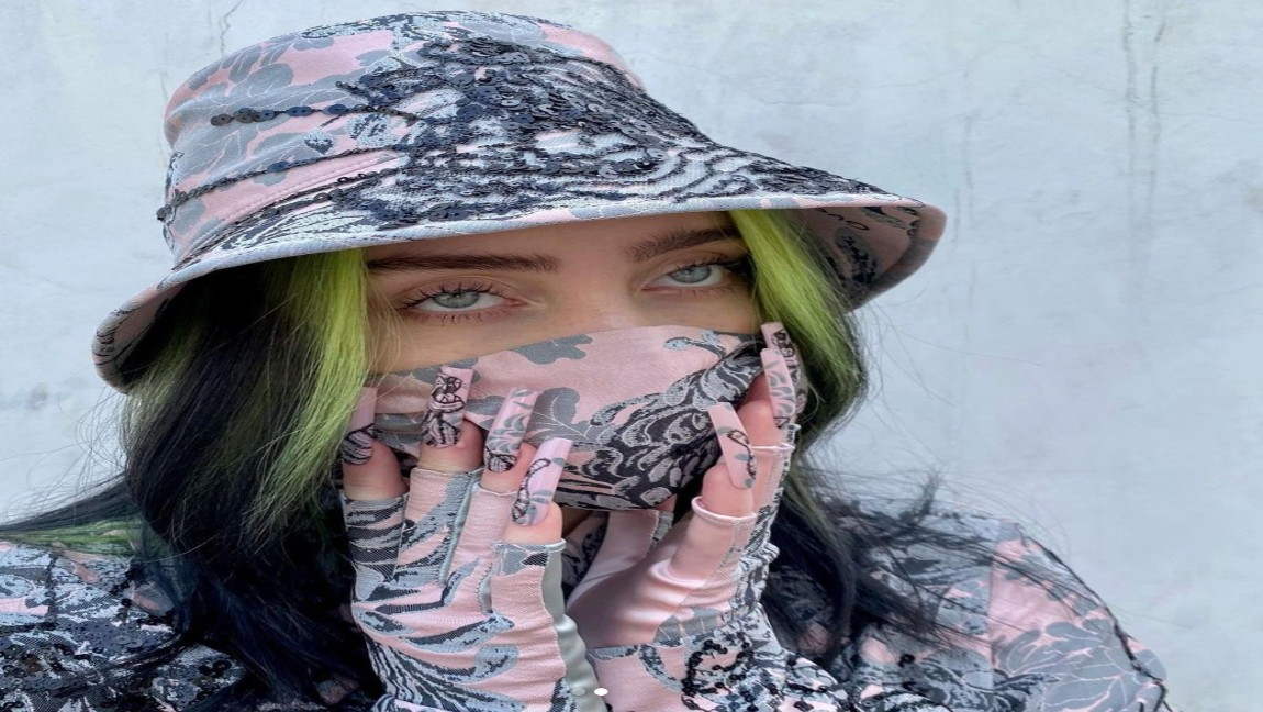 [image description: A young woman, Billie Eilish, wearing a mask and a hat]