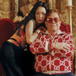 Rina Sawayama (left) leans on Elton John (right) whose hands are crossed before him while he wears red glasses. They are seated on red-backed chairs before a regal backdrop, staring into the camera.