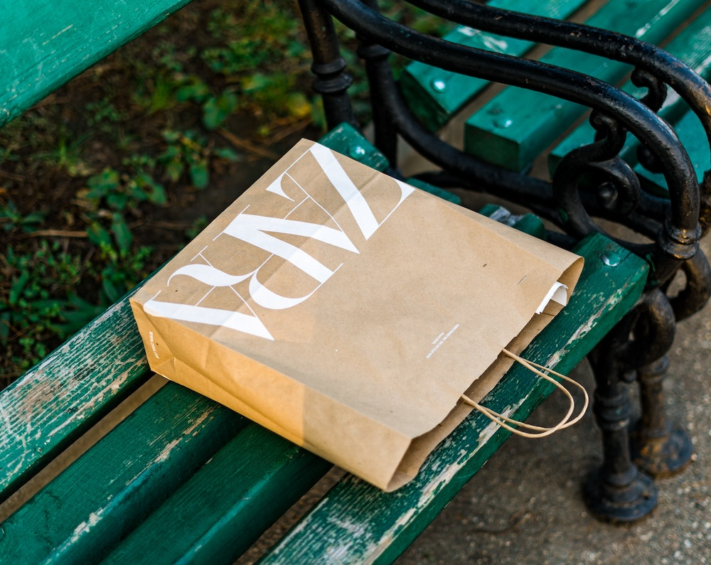 A brown shopping bag featuring the Zara logo is laid flat on a green park bench.