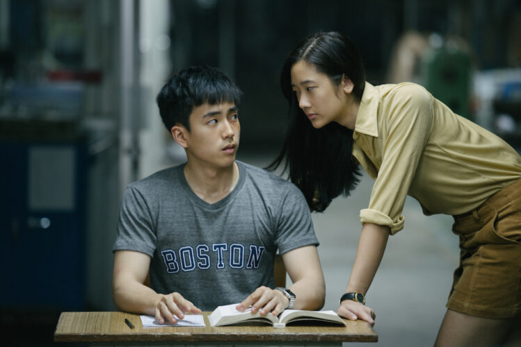 A male student looks warily at a girl leaning on his desk too-close-for-comfort who glares back at him.
