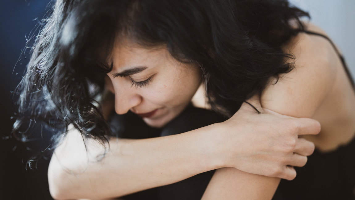 [Image description: Photo of a person bending over and hugging their knees.] Via Pexels