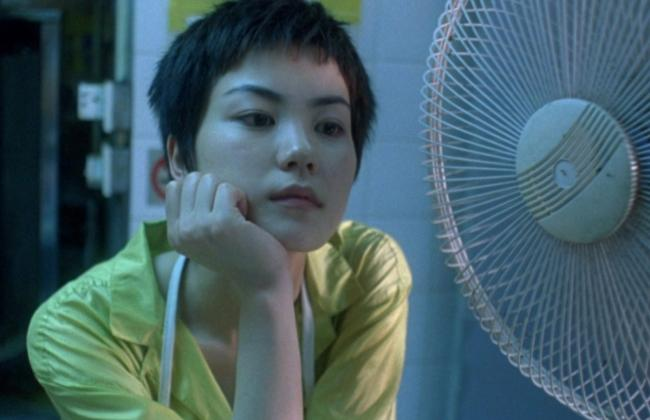 Convenience store worker Faye (Faye Wong) stares forlornly off-camera with her chin resting in her hand.