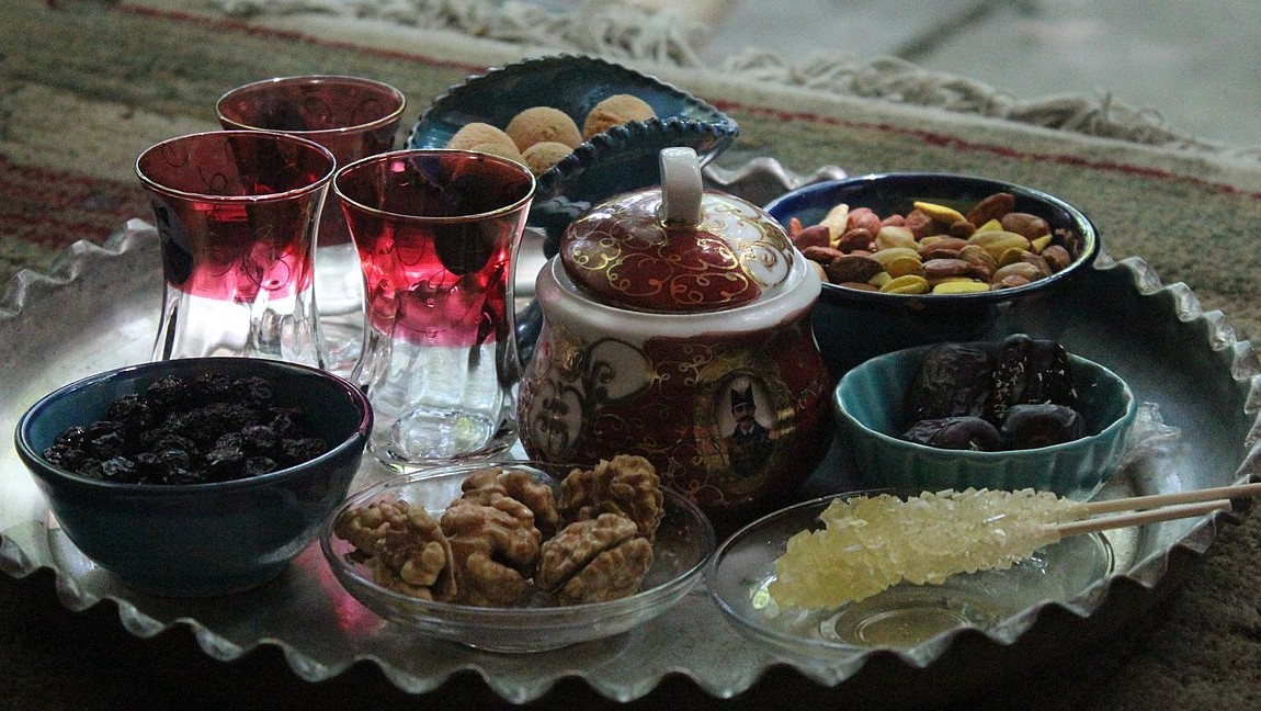 Tea served on a metal tray with dried cherries, dates, nuts, and cookies.