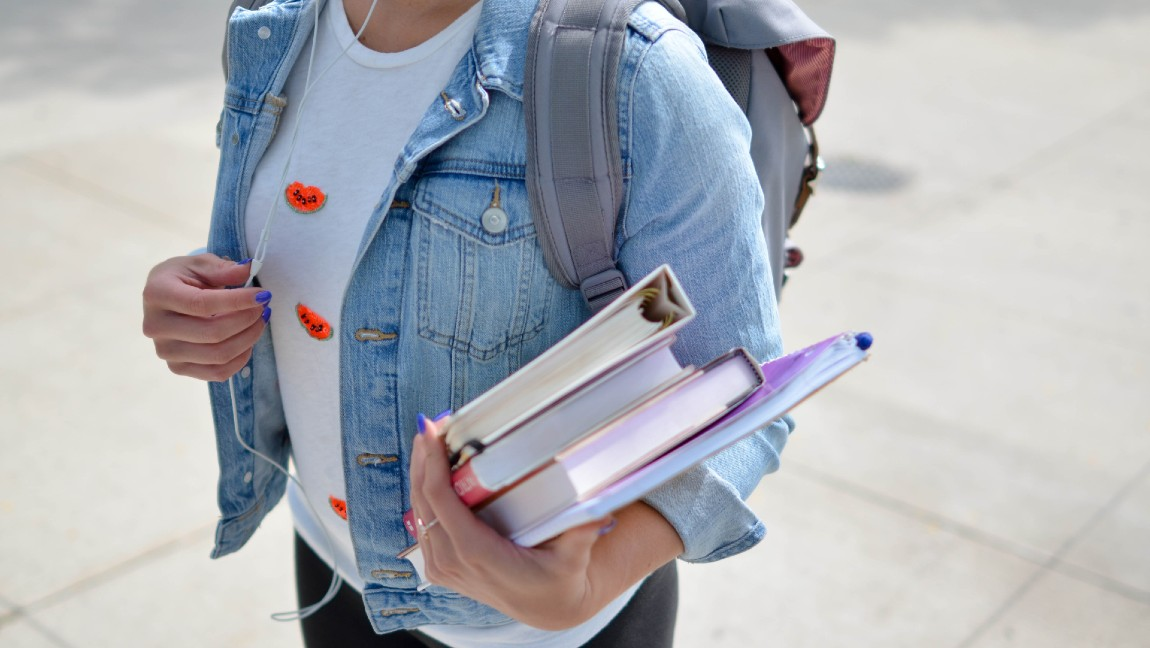 A woman in a denim jacket and white t-shirt is wearing a backpack, holding books in one hand and her earphones in the other hand.
