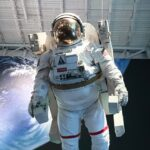 An astronaut is entering a spaceship and a part of the Earth can be seen behind them.