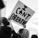 [Image Description: A protestor holding a sign that says I Can't Breathe] Via Unsplash