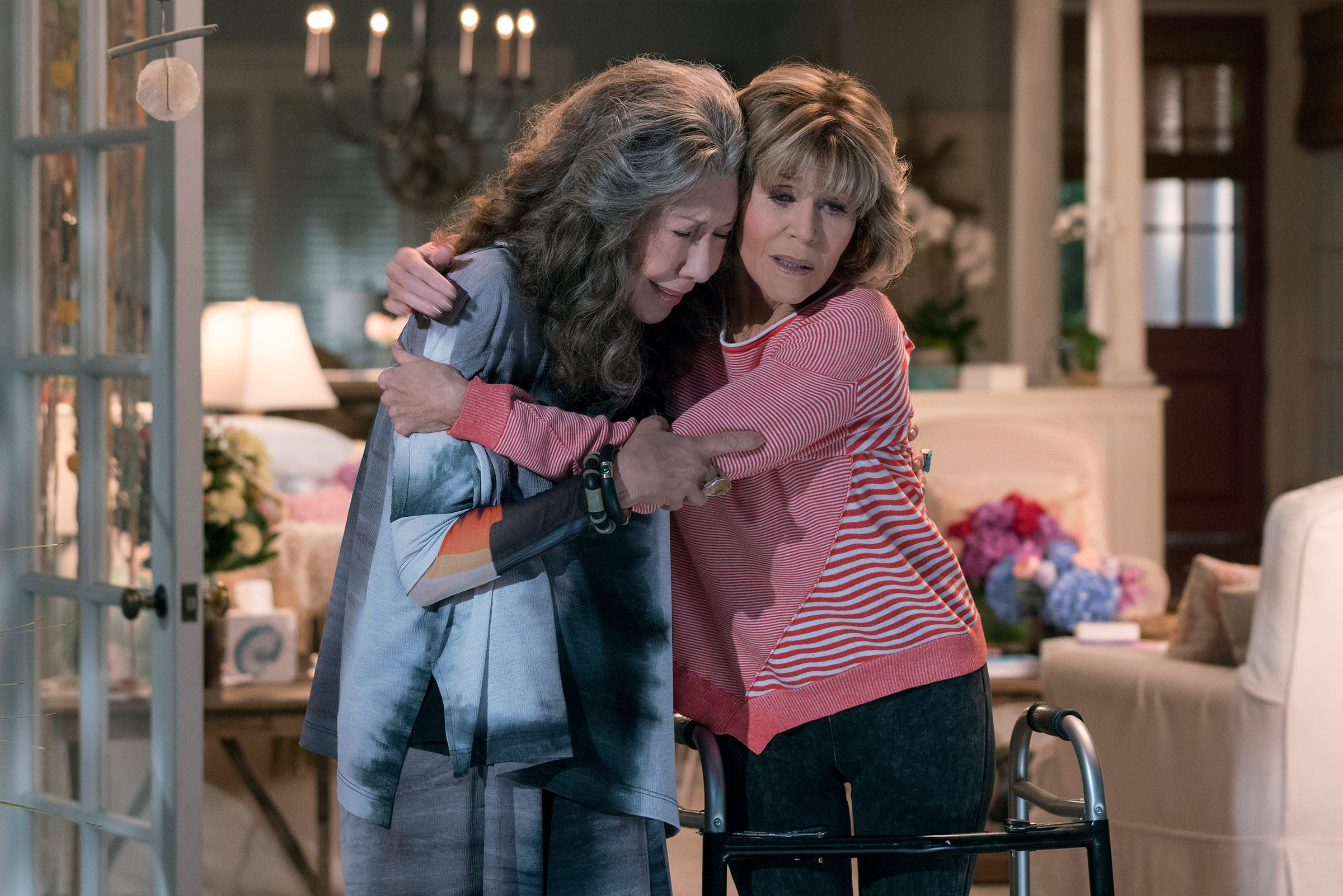 """Grace and Frankie from """"Grace and Frankie"""" hug in front of their beach house"""