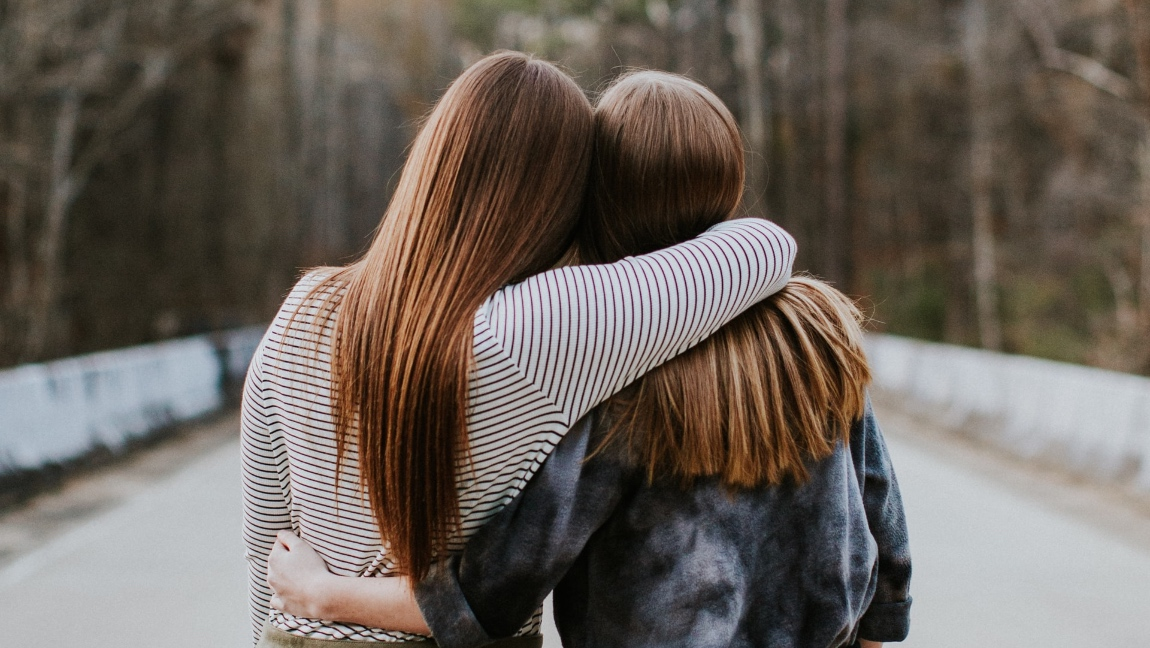 Two brunette woman hugging and looking into the distance.