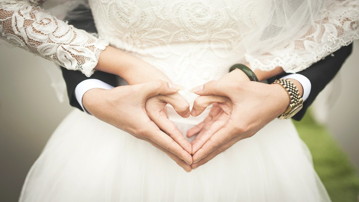 [image description: hands of a couple forming a heart together]