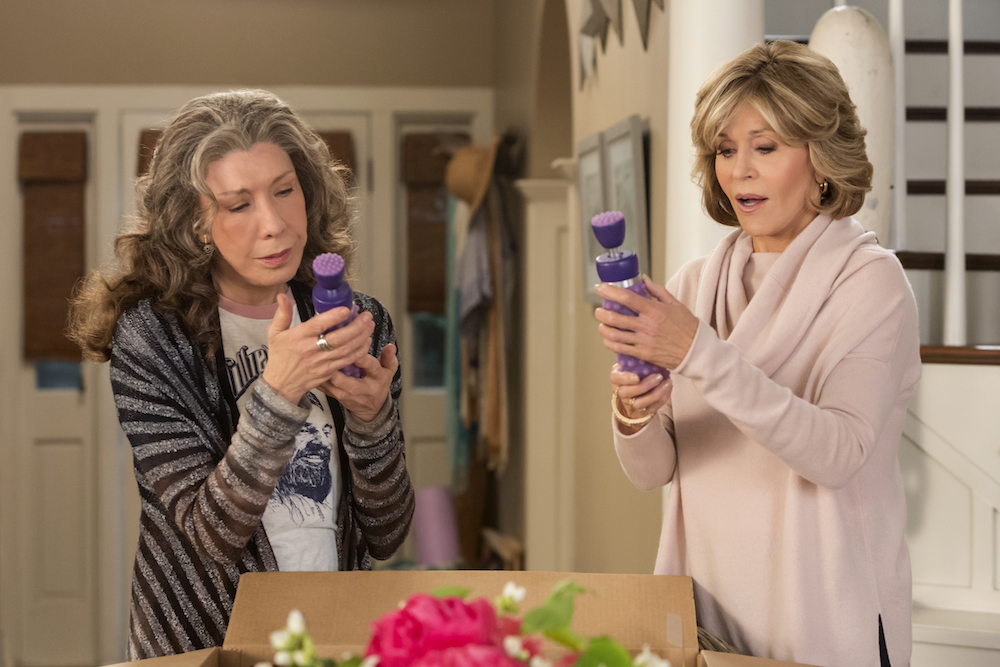 """Grace and Frankie from """"Grace and Frankie"""" holding up dildos from their brand Menage à Moi"""