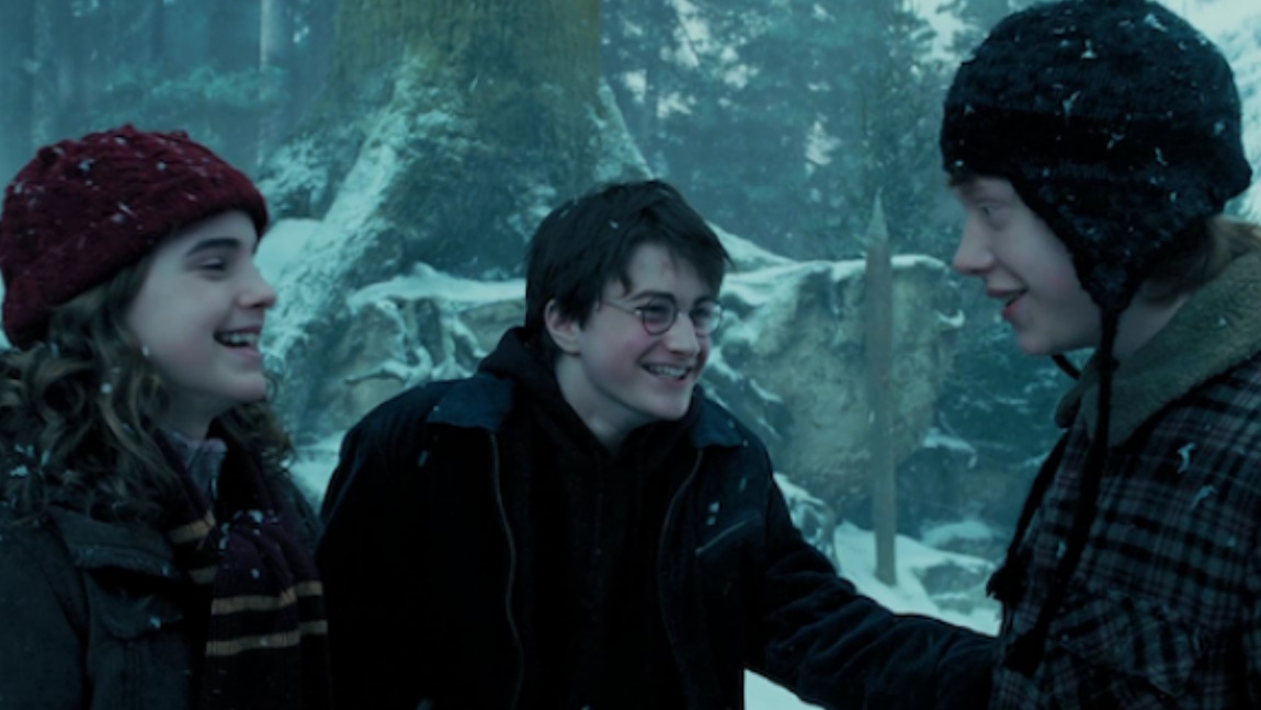 From left to right Hermione, Harry and Ron laughing in the snow.