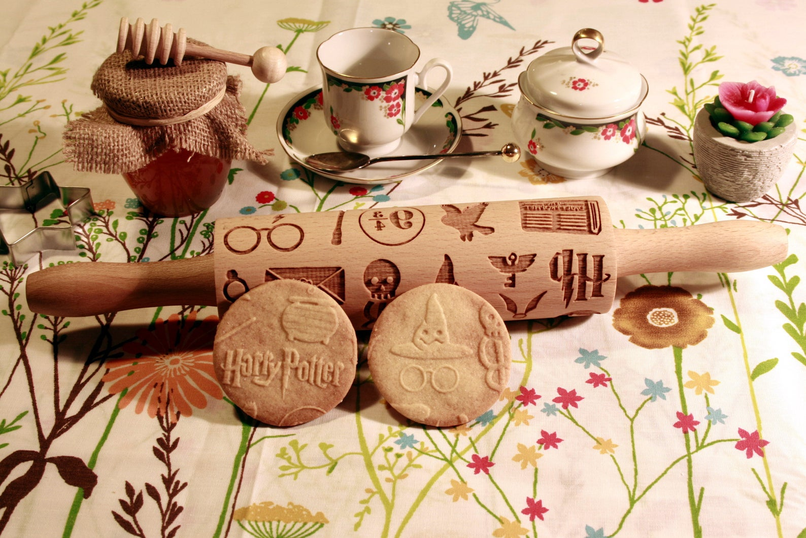 [Image description: a rolling pin engraved with Harry Potter symbols and two cookies embossed with some of the symbols] via Etsy