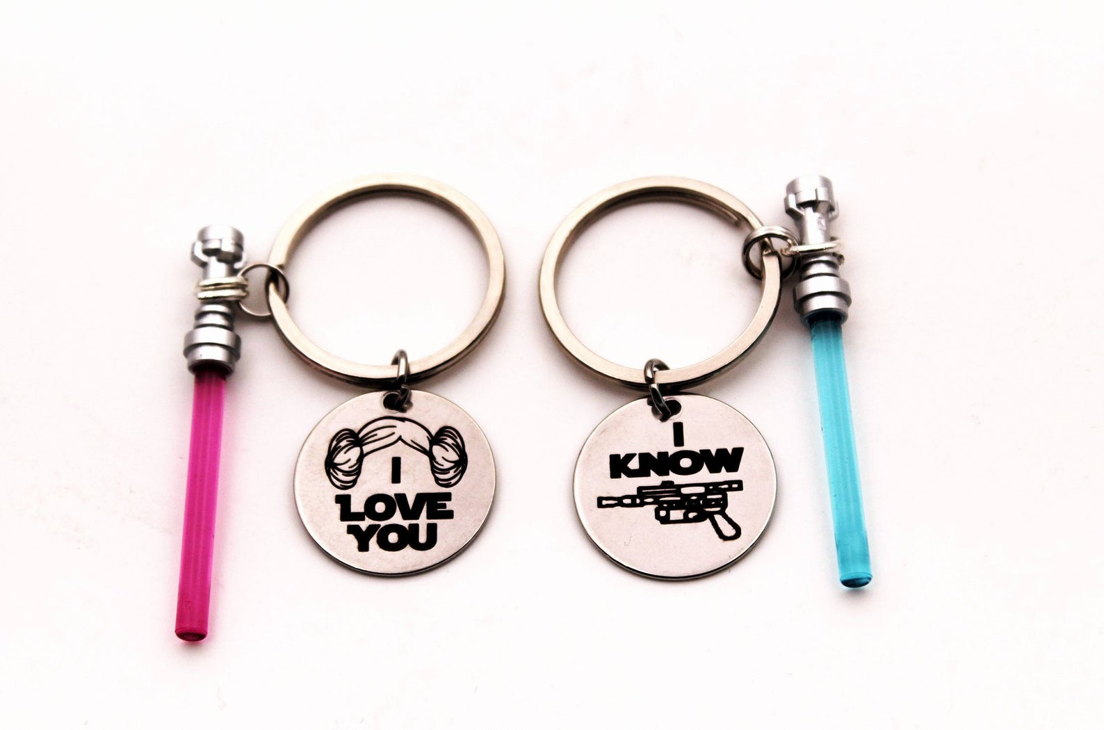 [Image description: two keychains. one has a pink lightsaber and 'I love you'. The other has a blue lightsaber and 'I know']