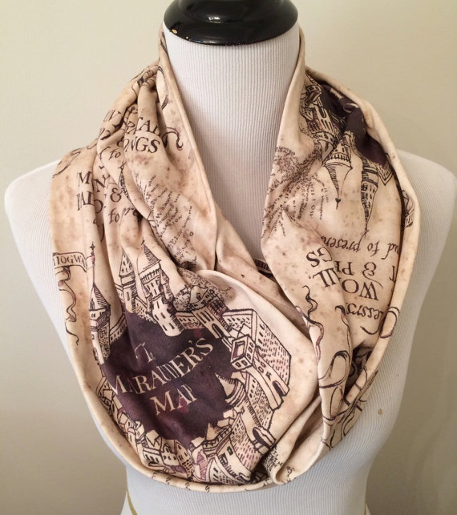 [Image description: a scarf depicting the Marauder's Map draped around the neck of a mannequin bust] via Etsy