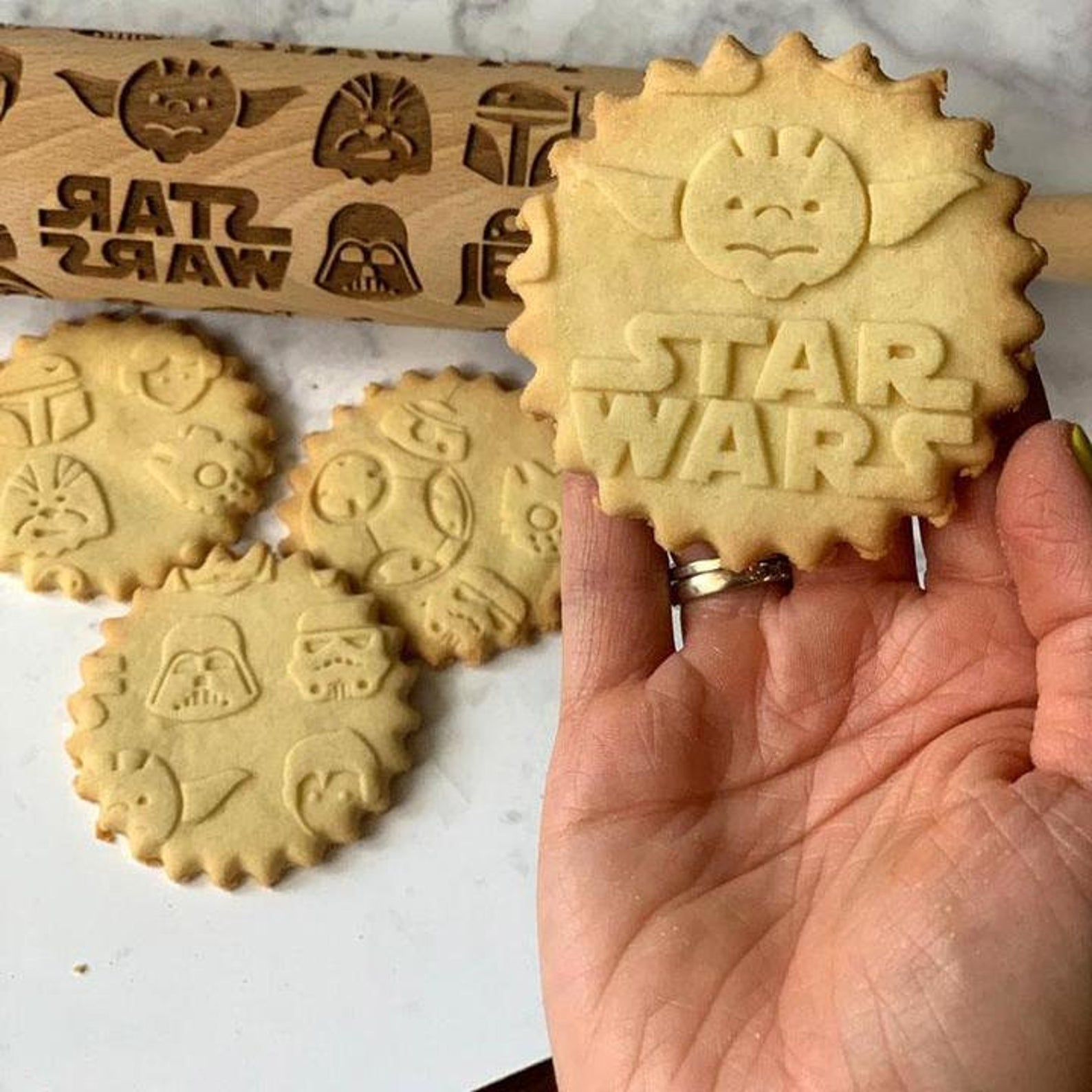[Image description: a rolling pin engraved with Star Wars symbols and 4 cookies]