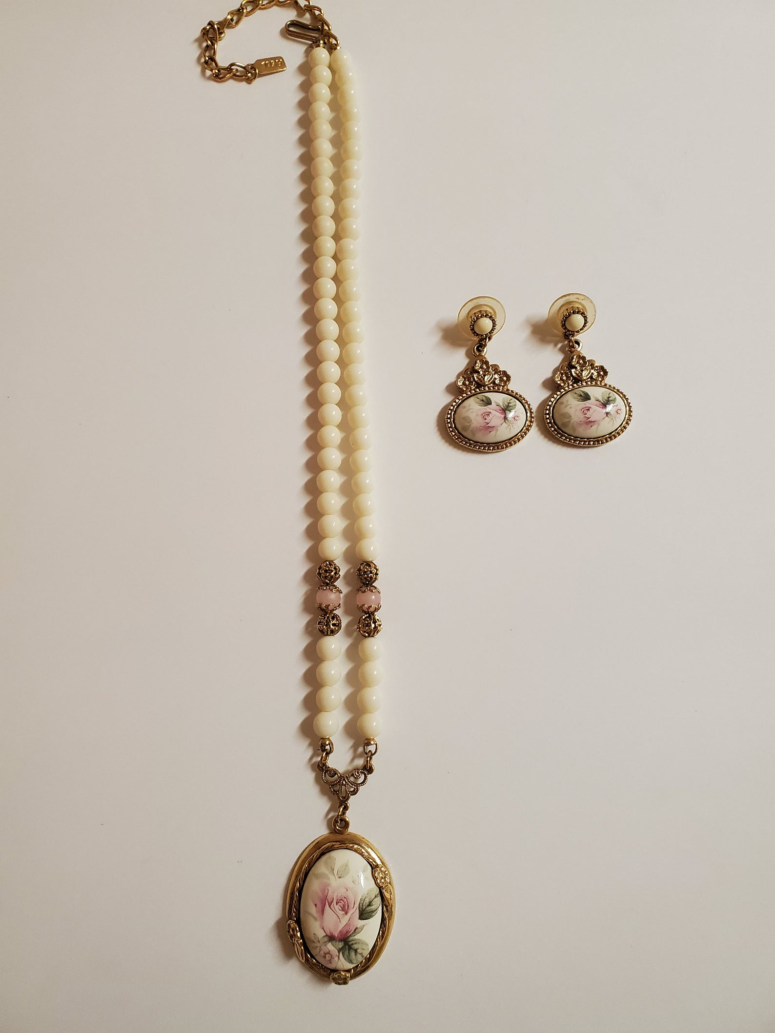 Necklace and earring set. Both are accented with pearls but the main focus is porcelain paintings of pink roses.