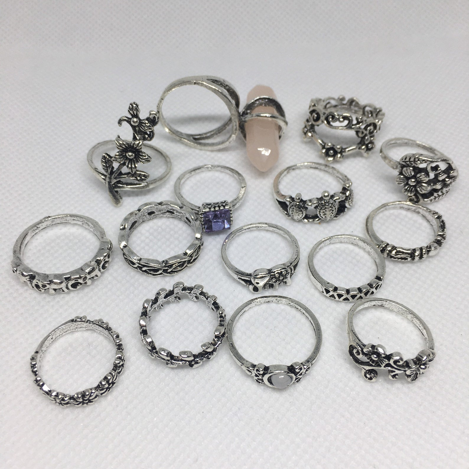 Assorted set of 15 bohemian rings. One has a pearl crystal hanging off it, another has a silver flower. Another has three consecutive turtles on the band. Many of them are simple silver rings with varied designs.