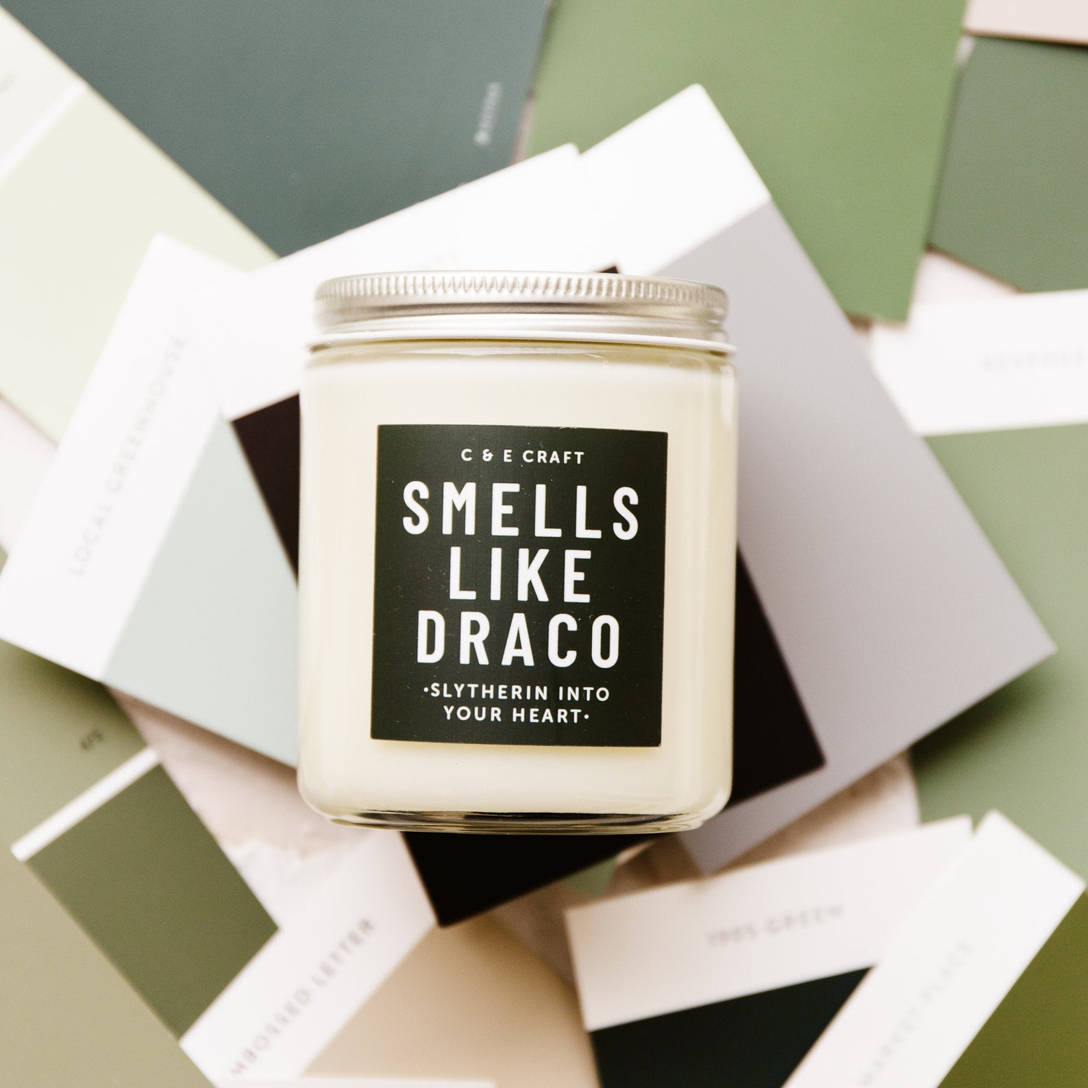 [Image description: a white wax candle in a jar with a label 'Smells like Draco' ] via Etsy