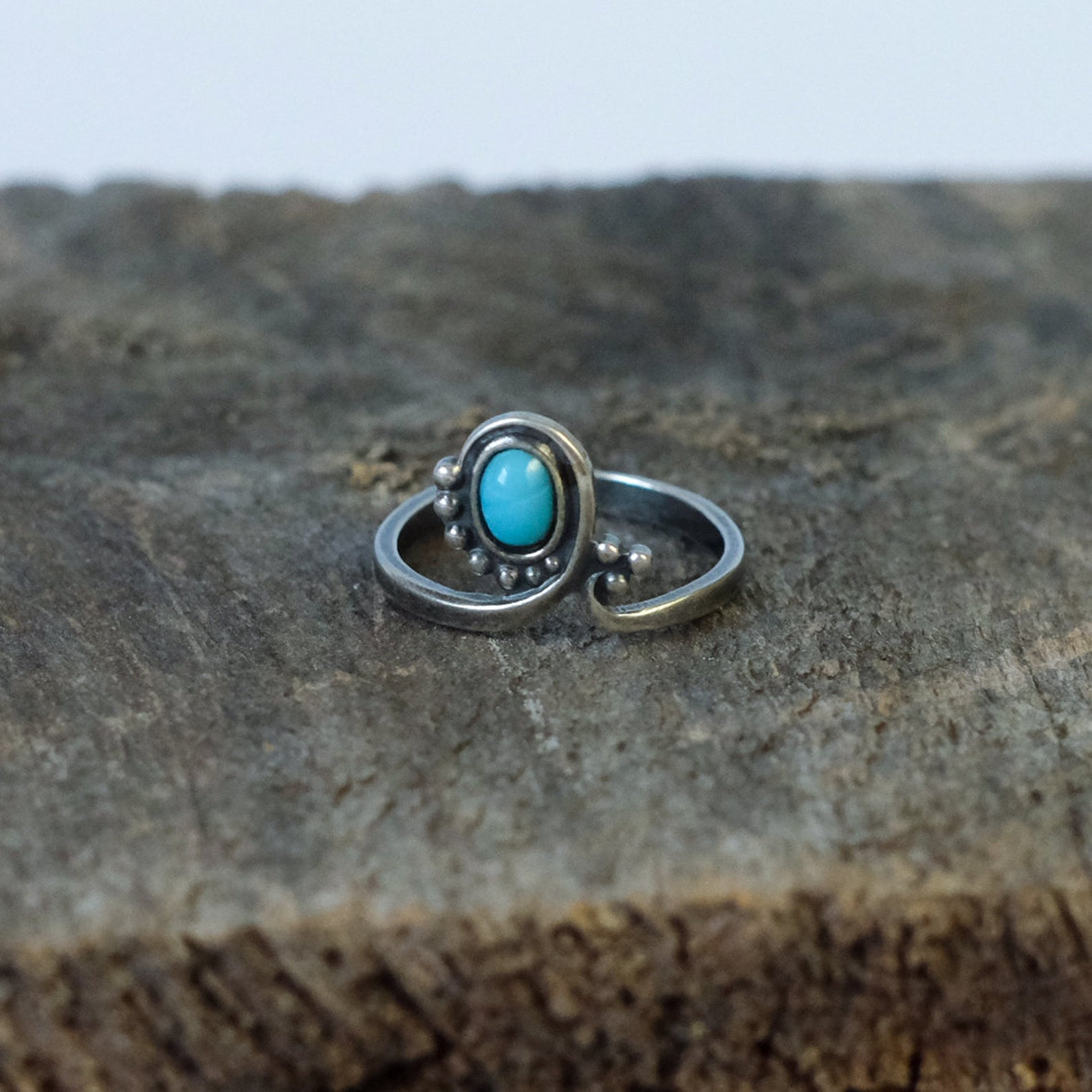 Vintage woman's ring with a turquoise gem. Hugged with a very vintage style silver shank.