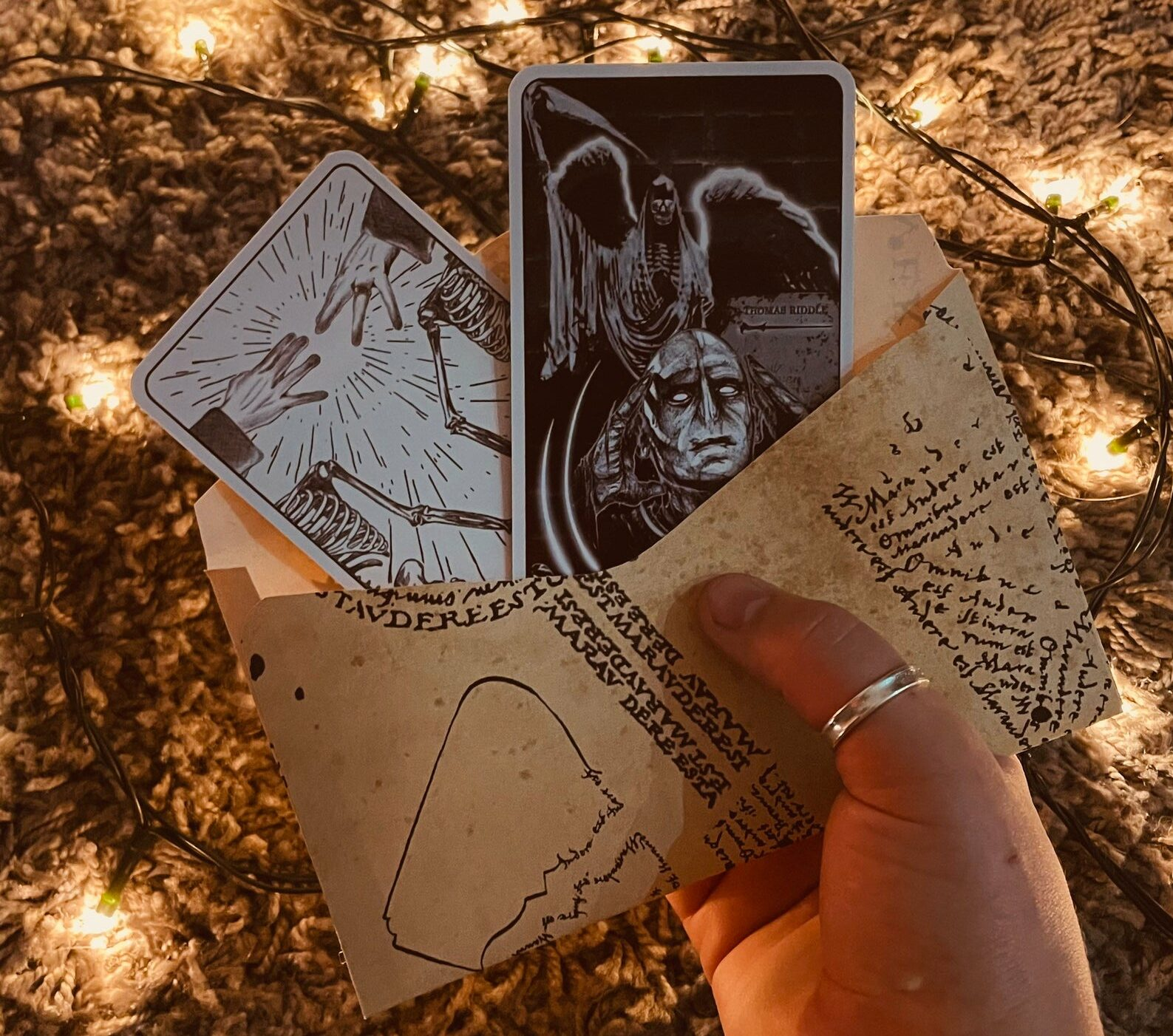 [Image description: a hand holds up an envelope with two tarot cards sticking out. The cards are designed in black and white ] via Etsy